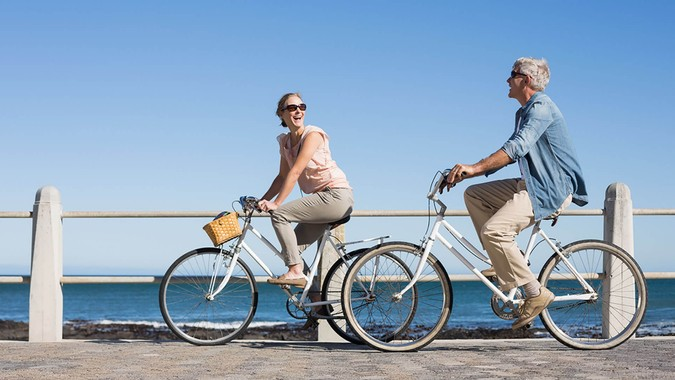 Happy casual couple going for a bike ride on the pier on a sunny day.