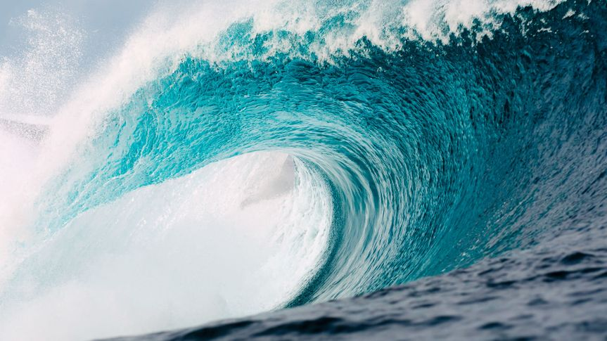 A perfect turquoise wave roars towards the coast.