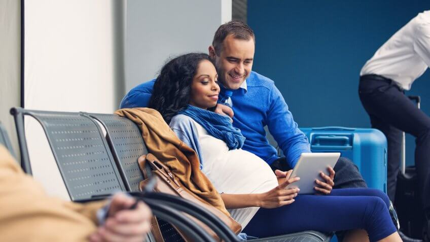 Pregnant woman waiting with her partner for the flight at the airport lounge, using a digital tablet together.