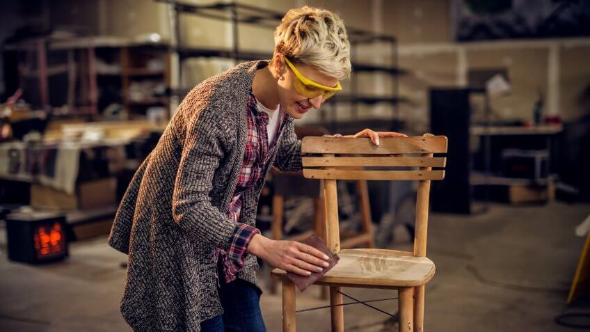 Attractive satisfied female furniture designer carefully sanding a chair frame with shelves of wooden items behind her in the workshop.