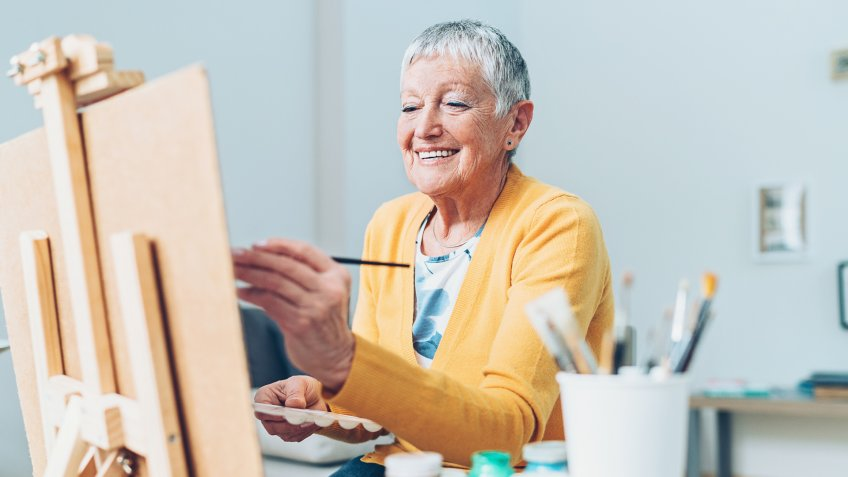 Senior artist woman drawing at home.