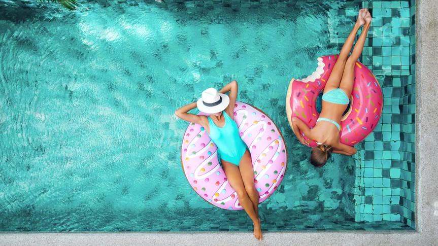 two women in blue swimming pool on innertubes