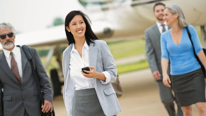 Business executives deboarding private corporate jet.