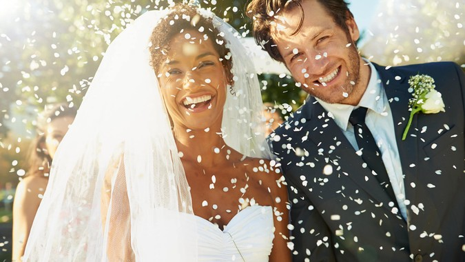 Shot of a happy newlywed couple being showered with confettihttp://195.