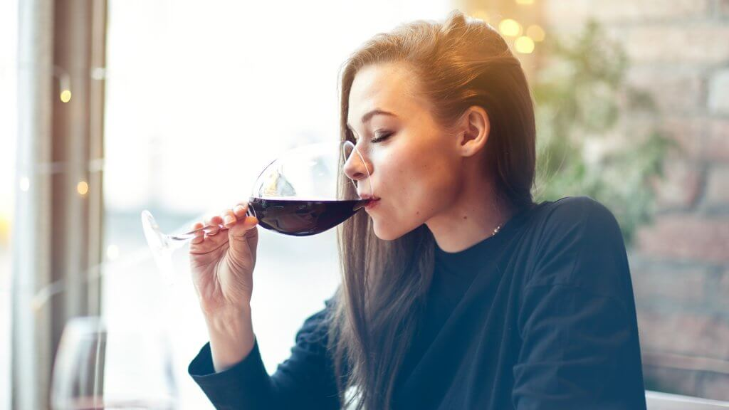 Beautiful young woman drinking red wine with friends in cafe, portrait with wine glass near window.