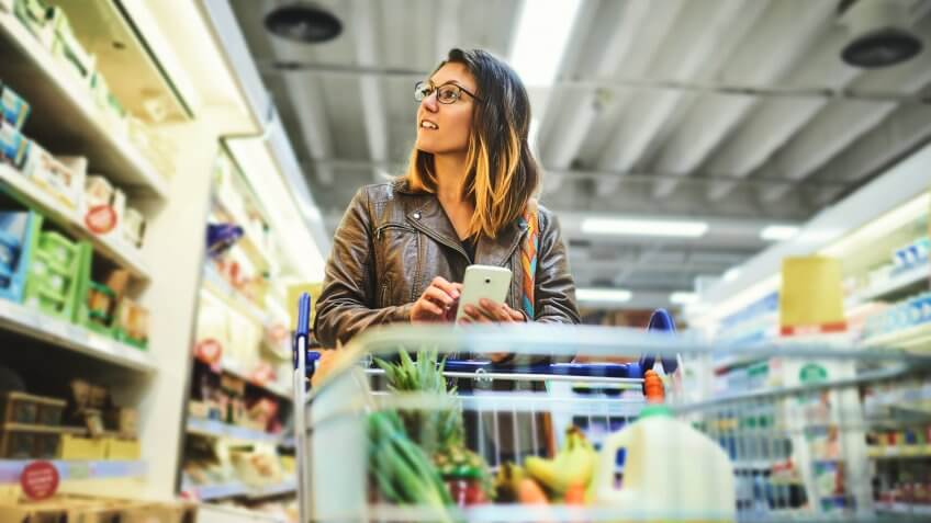 young woman using a mobile phone in a grocery store
