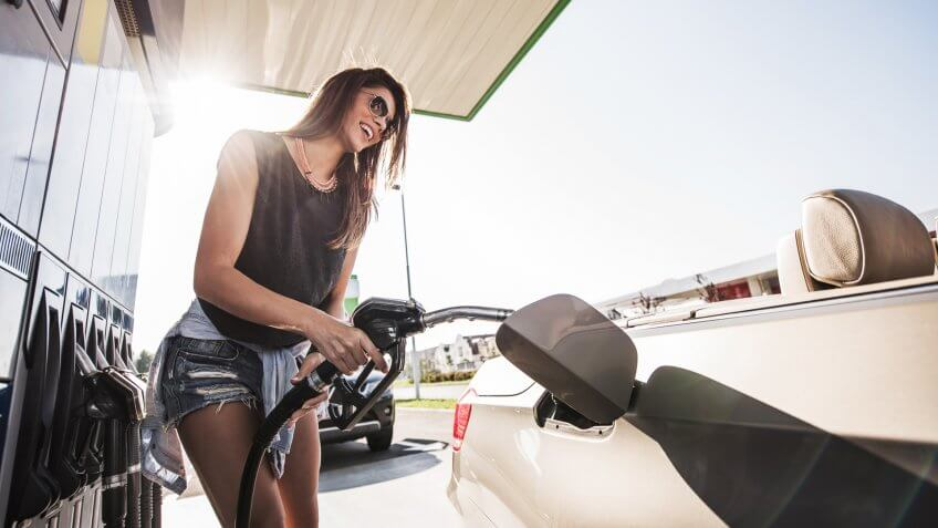 Below view of a young smiling woman refueling gas tank at fuel pump.