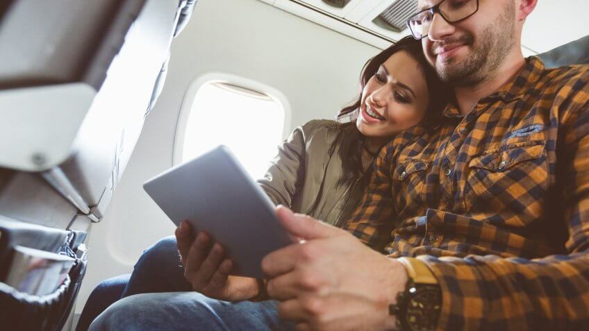 Happy young couple traveling by plane with digital tablet.