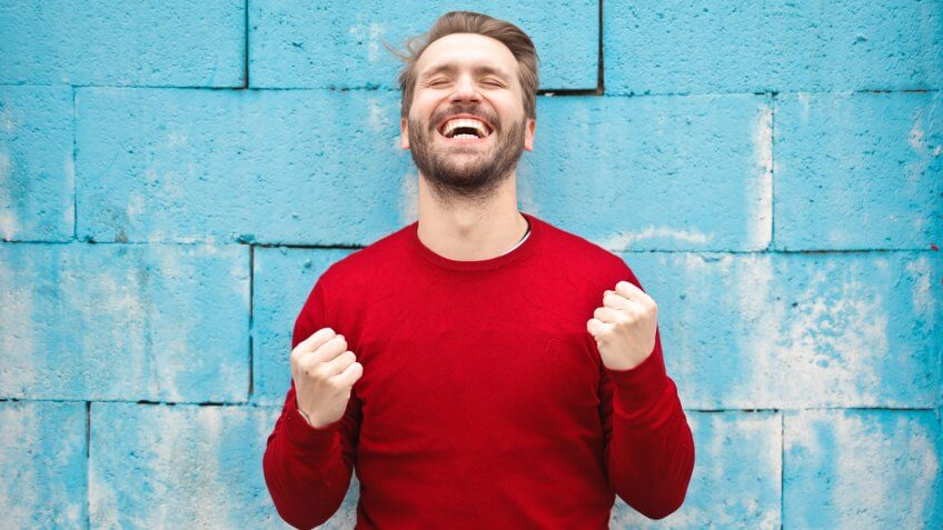 Smiling man in red sweater against blue wall making happy victorious gesture