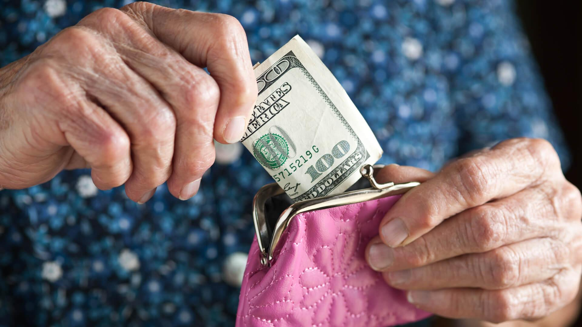 Senior Adult holding a one hundred dollar bill and a pink change purse.