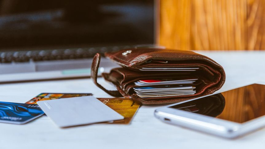 Wallet stuffed with credit cards sitting on a desk with a smartphone and laptop in the background