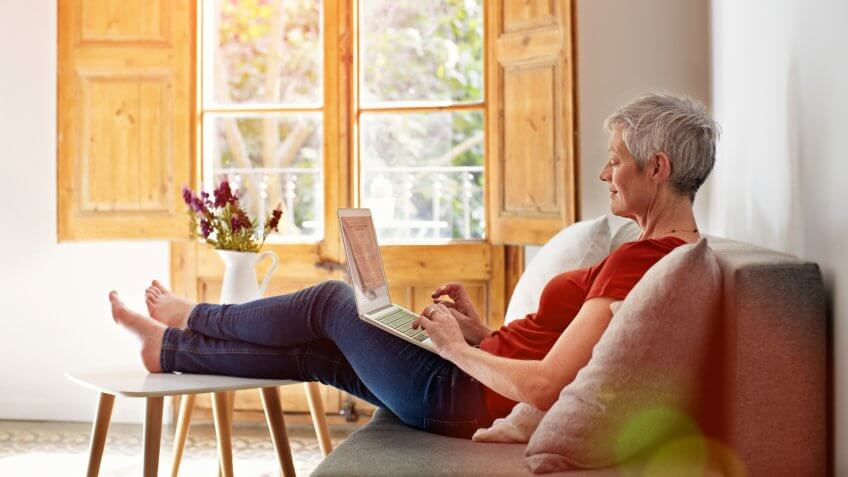 Shot of a mature woman relaxing on her sofa at home using a laptop.