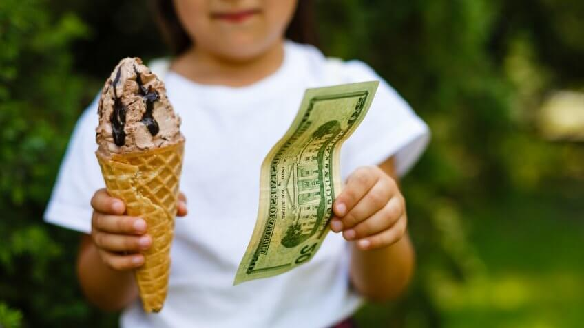 Little girl exchanging ice cream for dollar.