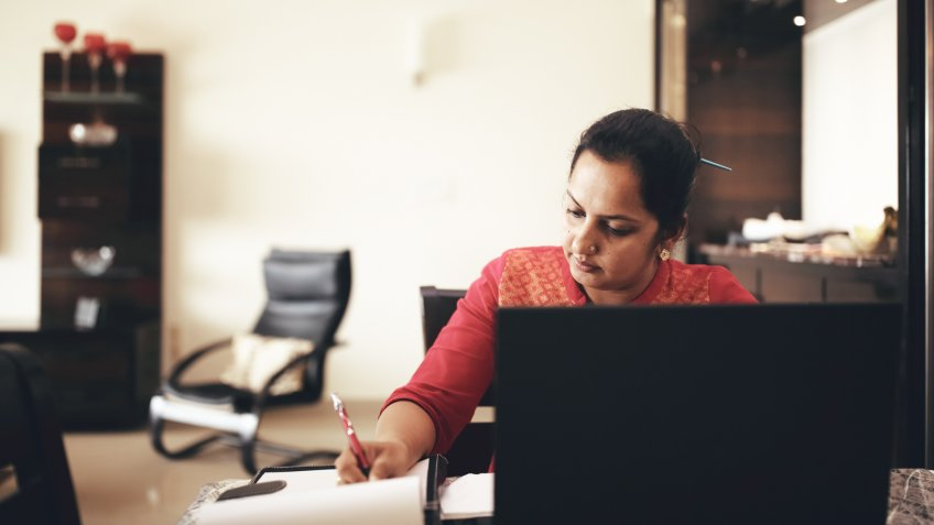Mid-age woman working at home, using laptop and writing in notepad.