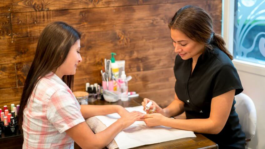 Happy woman getting a manicure at the beauty salon - casual lifestyle.