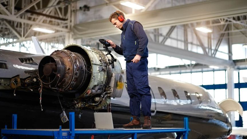Aircraft engineer in the hangar repairing and maintaining airplane jet engine.