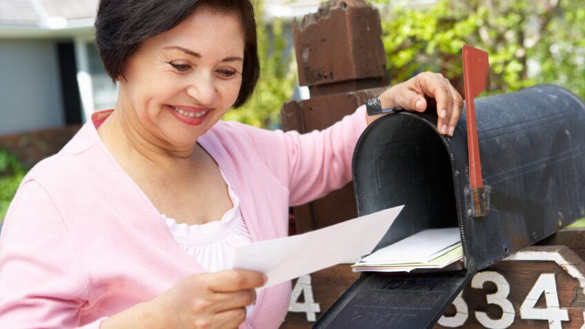 Senior woman looking at check received in the mail