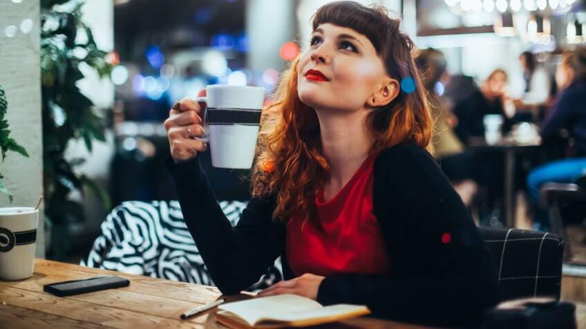 Woman Writing Journal at Window Seat in Coffee Shop.