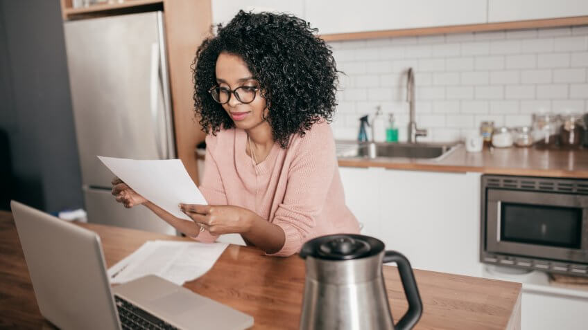 Woman taking care of finances at kitchen counter