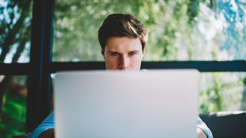 Man behind laptop focused on viewing the screen