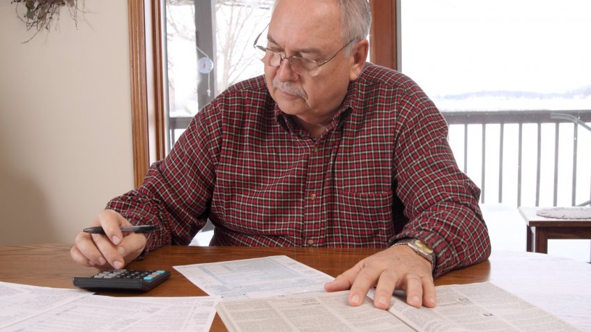 60s, Adult, Color Image, Document, Frowning, Gray Hair, Holding, Home Interior, Horizontal, Indoors, Looking Down, Male, Mature Adult, Men, Mustache, Objects, One Person, Only Man, Portrait, Preparation, Senior Adult, Senior Men, Serious, Table, Tax, calculator, casual, glasses, pen, sitting, tax form, window, working