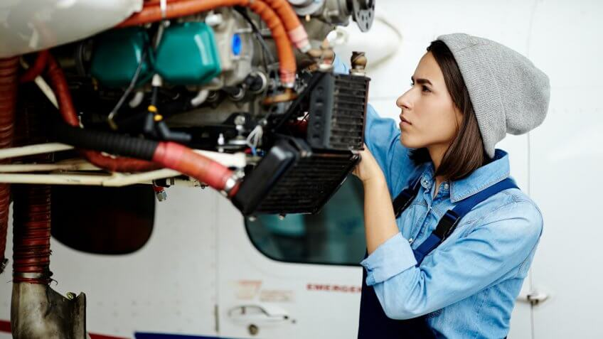 Young woman in uniform fixing something in air jet motor.