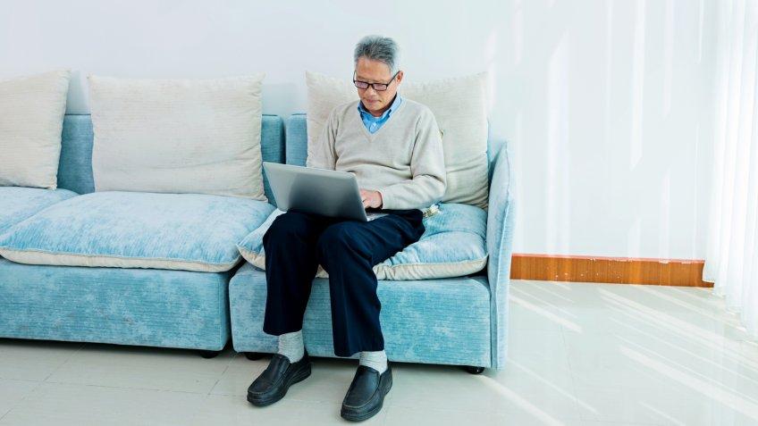 Senior asian man working on laptop at home.
