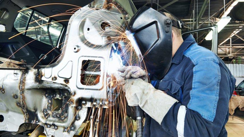 Automotive Industry worker welding vehicle metal
