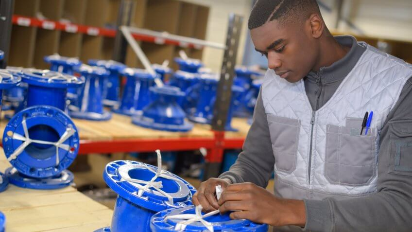 Young man working on parts for a vehicle in the automotive industry