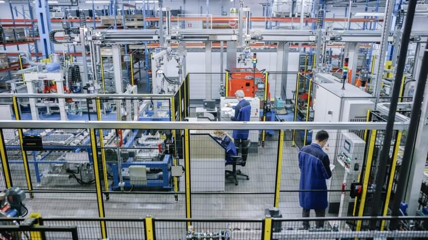 Factory workers working on production line in appliance manufacturing factory.