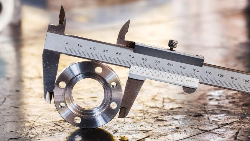 Close up vernier caliper measure diameter of stainless steel flange.