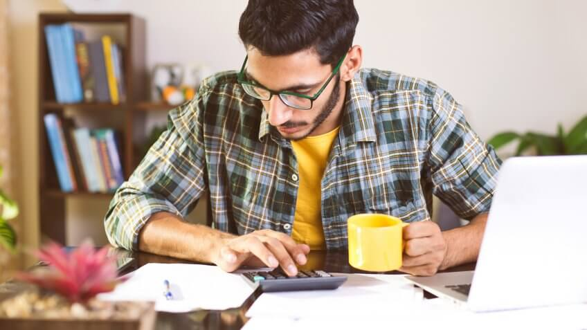 Man using calculator to calculate financial bills in home office.