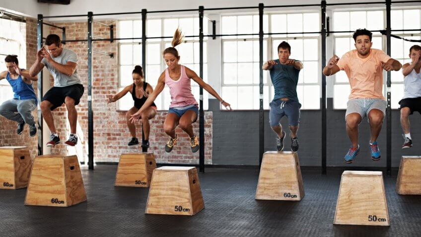 Shot of a group of people jumping onto boxes in a gym class.