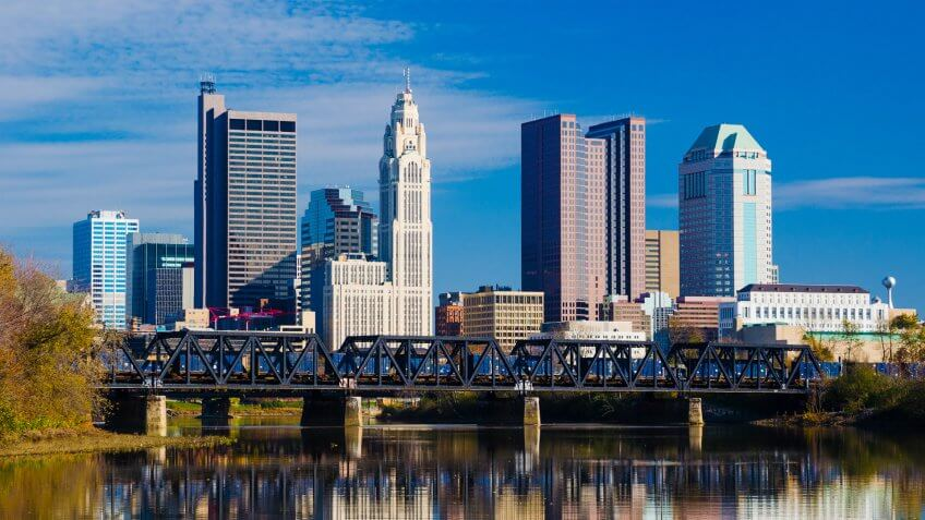 Downtown Columbus skyline, a train bridge, and the Scioto River with skyline reflection in the foreground.