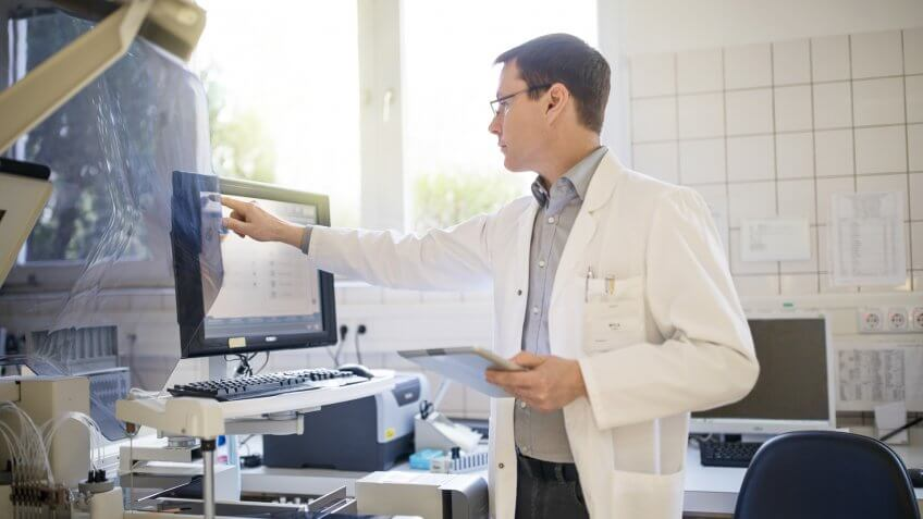 Male scientist using computer at hospital.