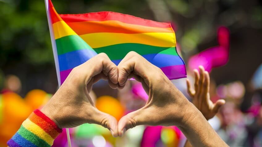 Supporting hands make heart sign and wave in front of a rainbow flag flying on the sidelines of a summer gay pride parade.