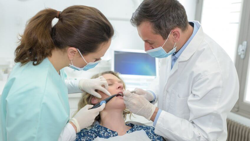 Oral surgeon and assistant operating on a patient's teeth