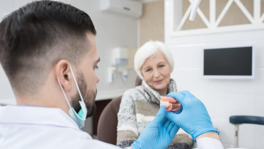 Professional male dentist in gloves showing dentures teeth to senior female patient and explaining how to use it in dental surgery.