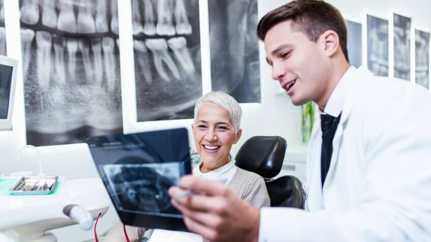 Dentist checking x-ray image or scan while beautiful senior woman receiving a dental treatment.