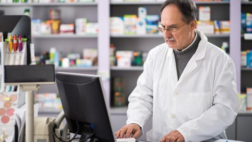 Senior pharmacist using desktop PC while working in a pharmacy.