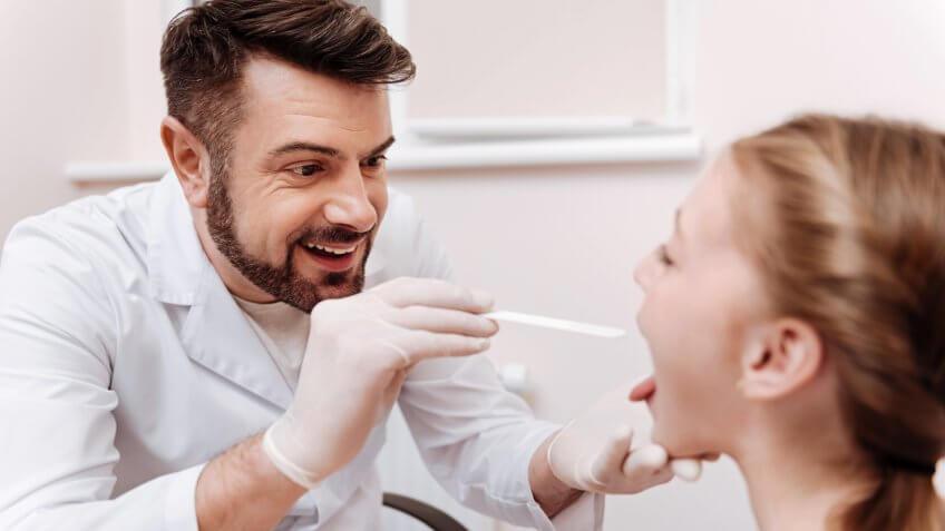 Attentive nurse practitioner conducting throat exam