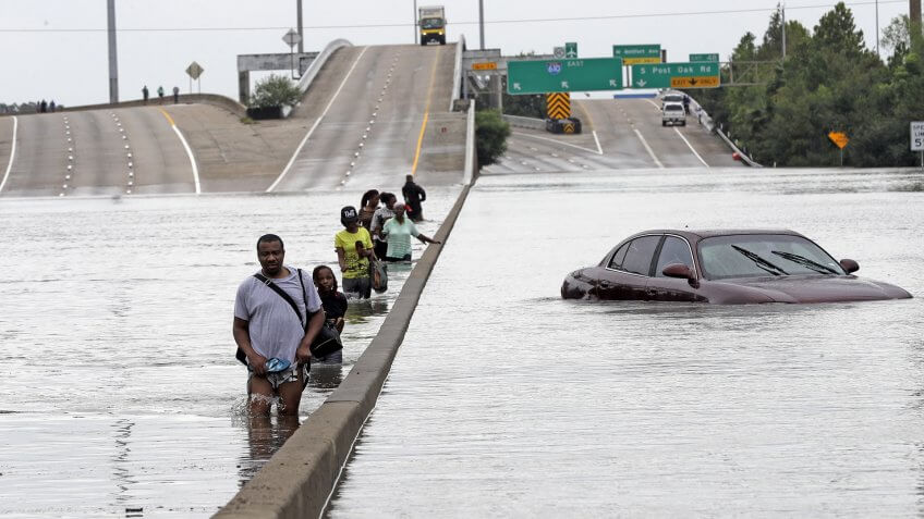 Photo by AP/REX/Shutterstock (9028178a)Evacuees wade down a flooded section of Interstate 610 as floodwaters from Tropical Storm Harvey rise, in Houston.