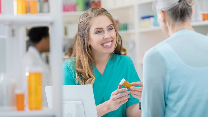 Smiling young pharmacist talks with senior patient