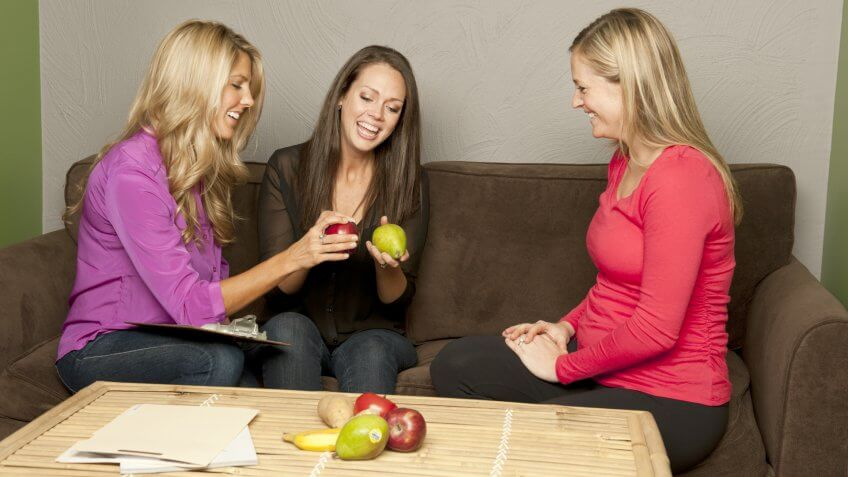 Nutritionist and dietetic technician explaining the benefits of fruits to a patient