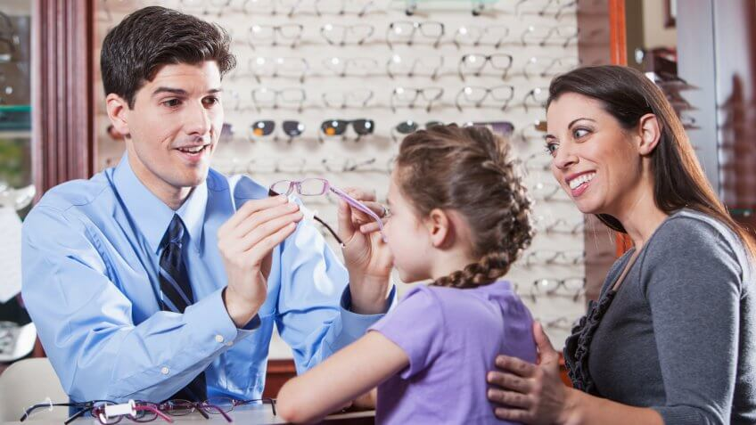 Optician helping little girl try on new glasses while mother watches