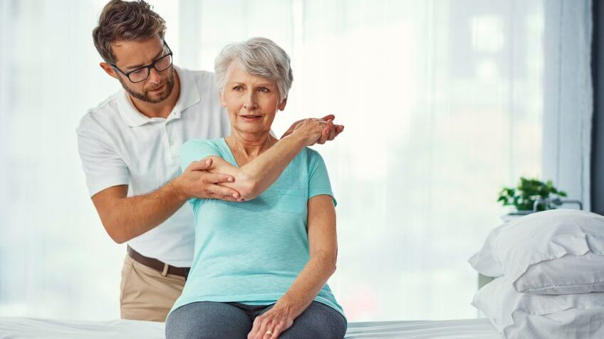 Exercise physiologist assisting senior woman with recovery
