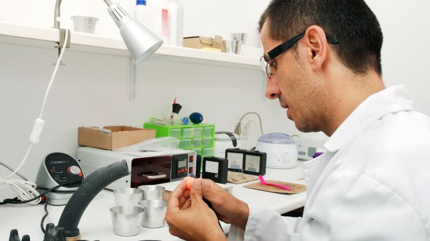 Hearing aid specialist working on custom made ear plugs, used for patients with ears prone to infection through water contact.