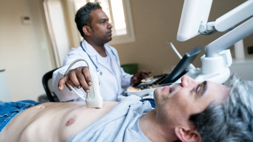 Cardiovascular Technologist doing a heart ultrasound to a middle aged male patient at the hospital.