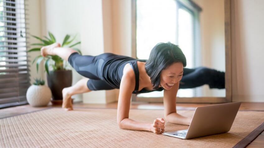 Woman exercising at home following a fitness video online.
