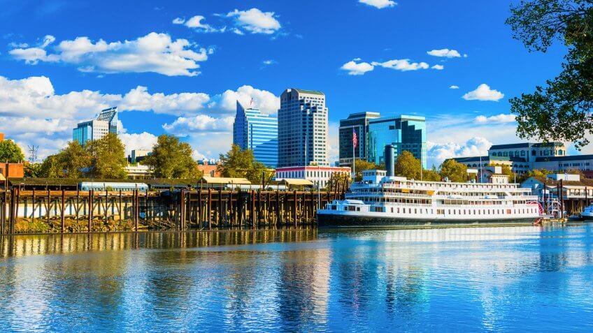 Downtown Sacramento skyline with the Sacramento River and the historic Delta King riverboat in the foreground and puffy white clouds and a deep blue sky in the background.
